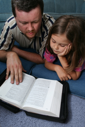 Christian father reading bible with daughter